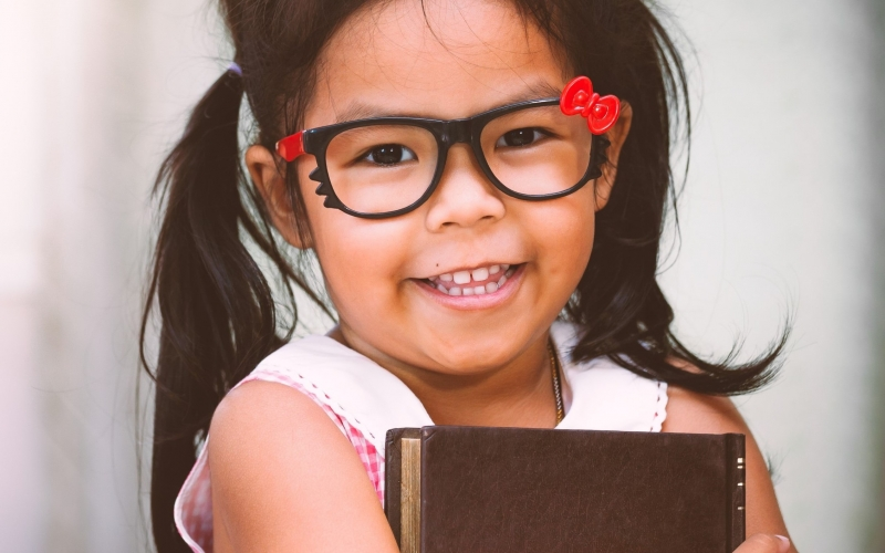 Little girl with pigtails and glasses holding a book