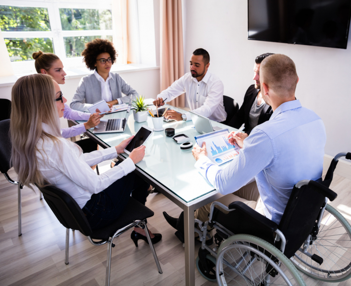 A team meeting around a work table including women of color, men of color, and a person in a wheelchair